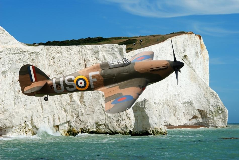 Un avion de vânătoare de tip Spitfire care survolează coastele maritime ale Angliei