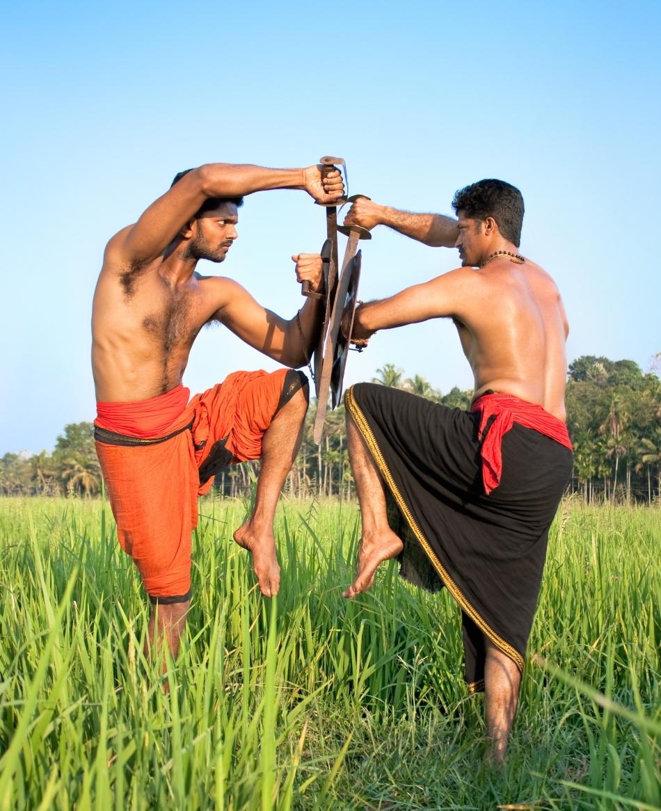 Doi practicanţi de Klaaripayattu care exersează o poatură specifică în lupta cu sabia şi scutul.