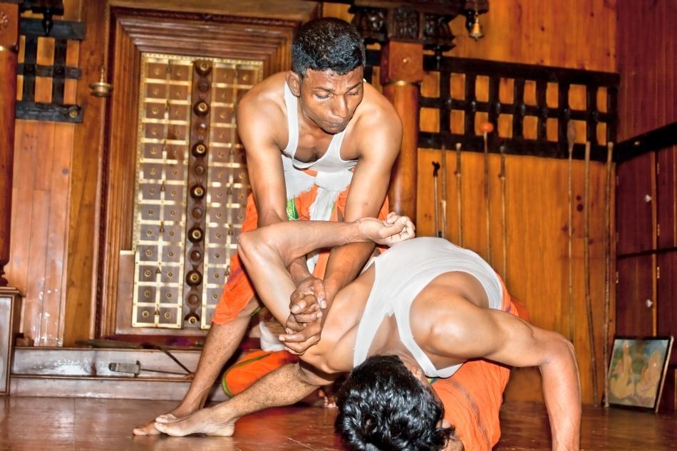 Un maestru de Kalaripayattu aplică o cheie de umăr unui practicant.