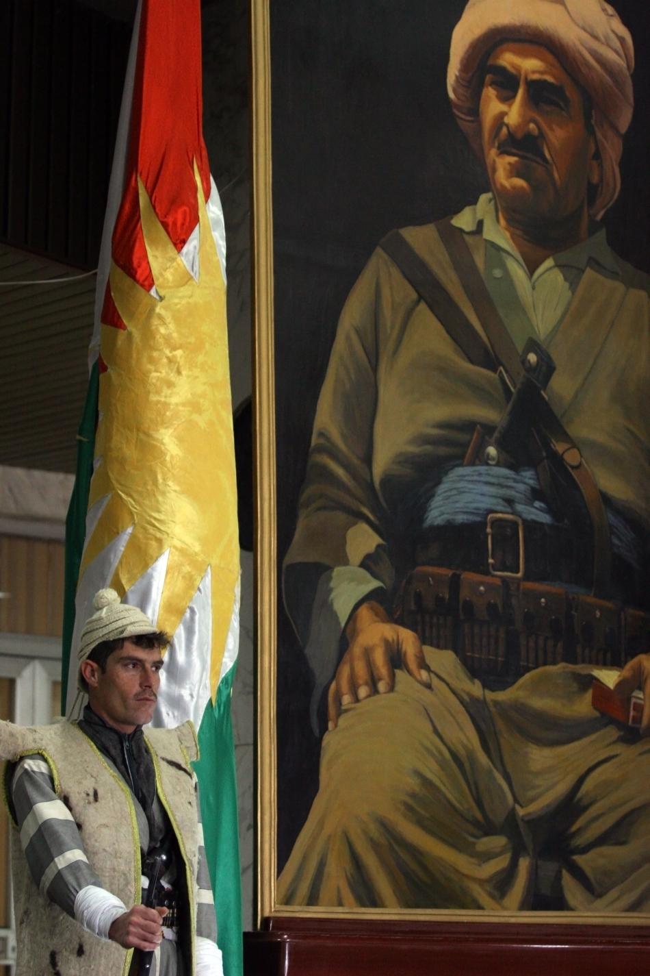 Soldat kurd care stă de pază în faţa portretului lui Mustafa Barzani, cel mai mare erou kurd.