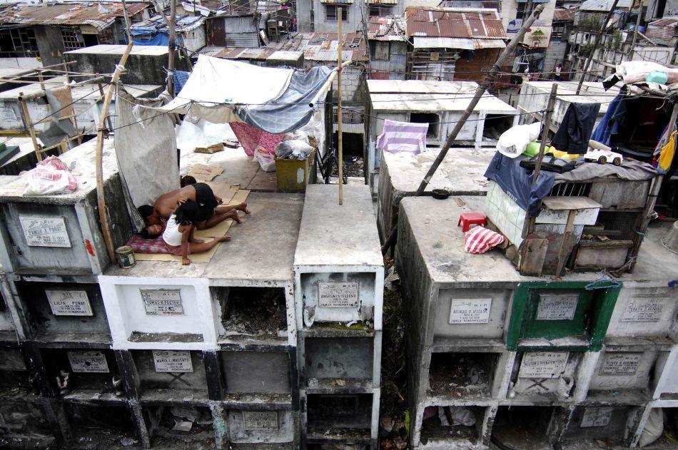 O familie locuişte în casa lor de tip baracă construită pe morminte în interiorul Cimitirului Municipal din Manila (Filipine), 30 Octombrie 2009