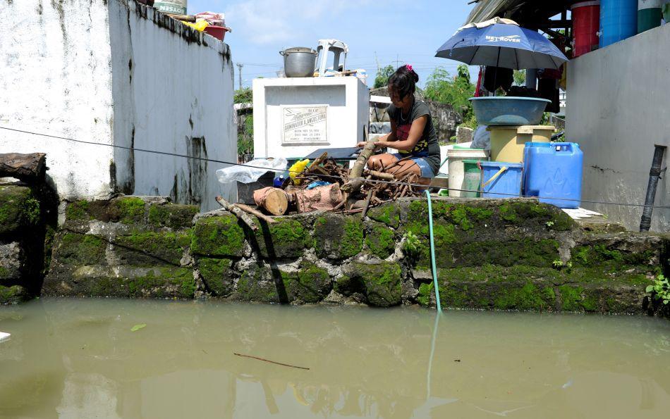 O femeie usucă lemne de foc lângă un mormânt ce a servit drept casă temporară a familiei sale în timpul inundaţiilor din oraşul Calumpit situat la nord de Manila (Filipine), 11 August 2012