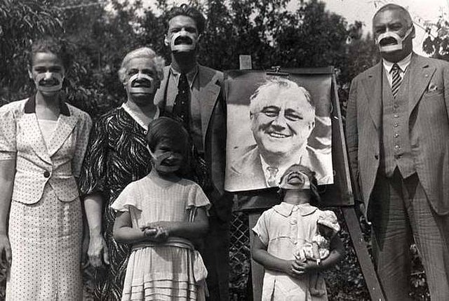 O familie se fotografiază purtând pe faţă masca unui zâmbet