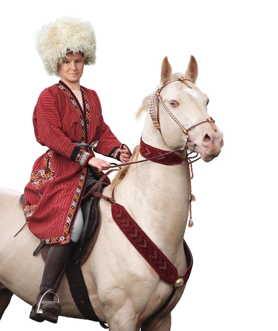 Un exemplar de culoare cremello deschis călărit de o persoană în costum tradiţional turkmen