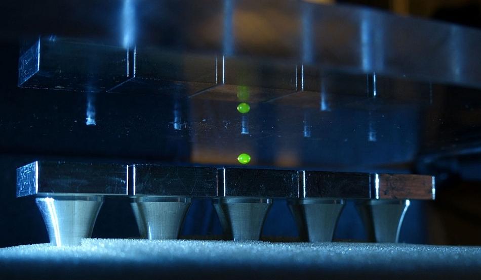 O picătură de lichid levitează între platformele ce emit sunete (jos) şi suprafaţa de sus ce reflectă sunetele