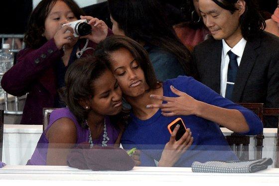 """Malia şi Sasha Obama au fost surprinse în timp ce realizau un """"selfie"""" la inaugurarea preşedintelui Obama"""