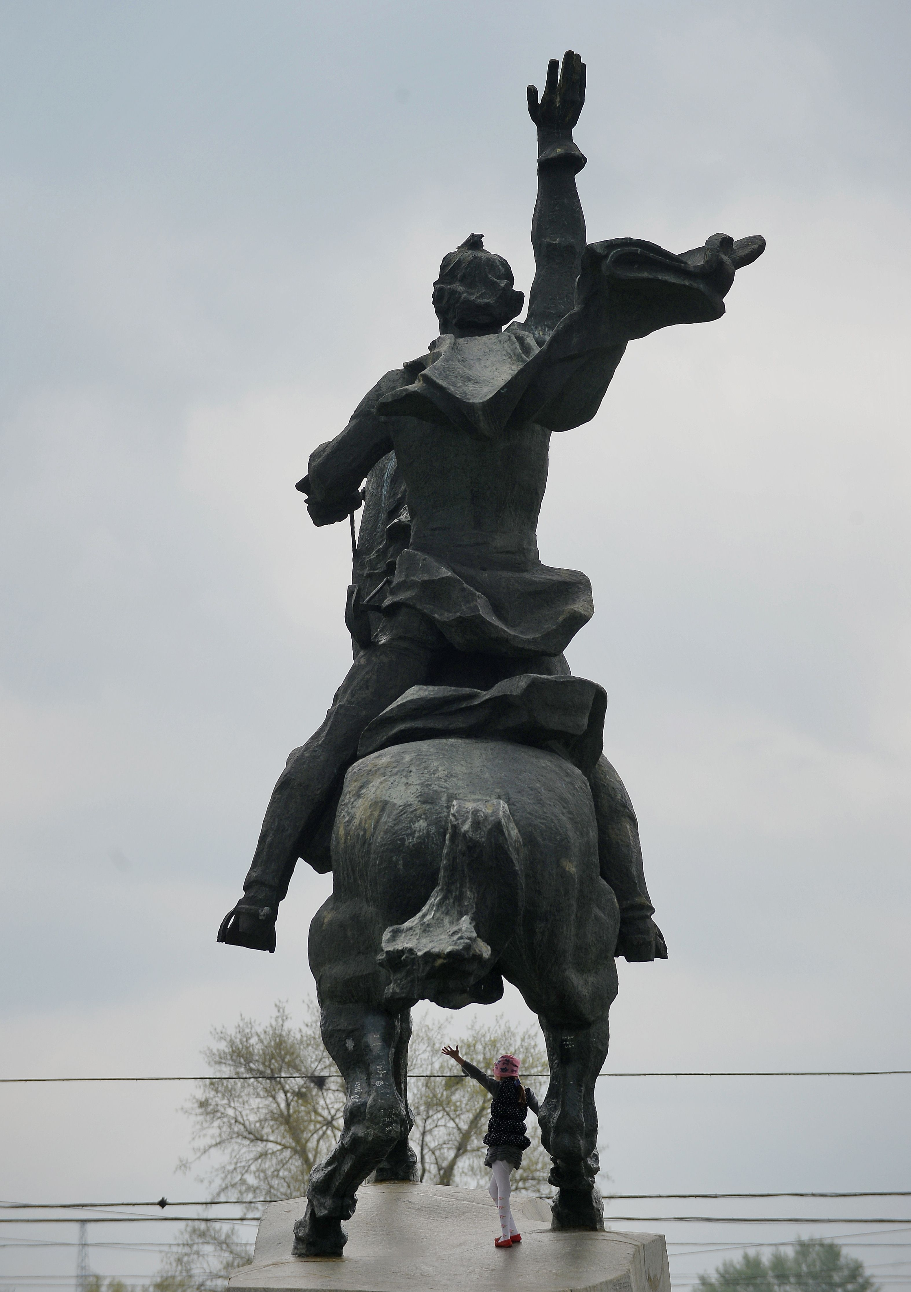 O fată se joacă sub statuia lui Aleksandr Suvorov