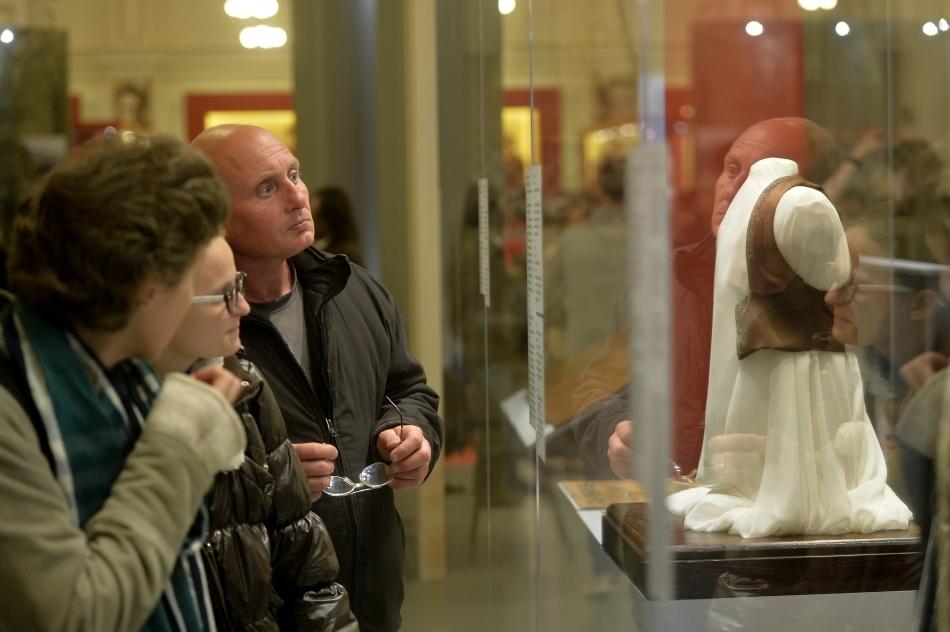 O femeie priveşte spre o vitrină în care sunt expuse piese vestimentare, într-o expoziţie din Muzeul Naţional de Istorie a României, în cadrul Nopţii Albe a Muzeelor, în Bucureşti, sâmbătă, 17 mai 2014.