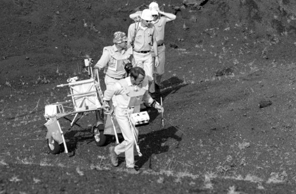 """Astronauţii Alan Shepard, Edgar Mitchell şi Stuart Roosa, membri ai misiunii Apollo 14, cară transportorul modular de echipament (MET), poreclit """"ricşa""""."""