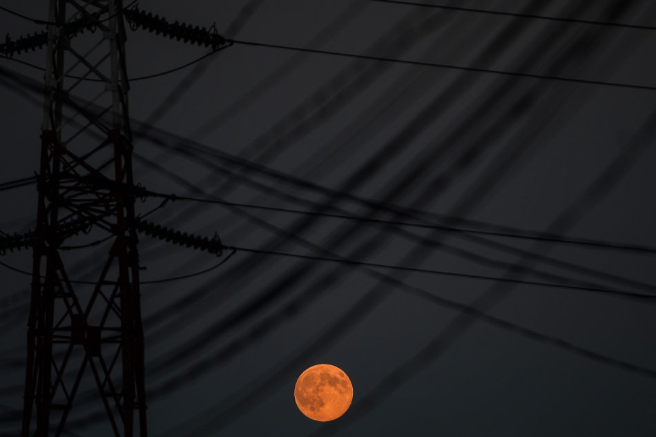 Luna plina poate fi observata printre fire de inalta tensiune, in Bucuresti, duminica, 10 august 2014.