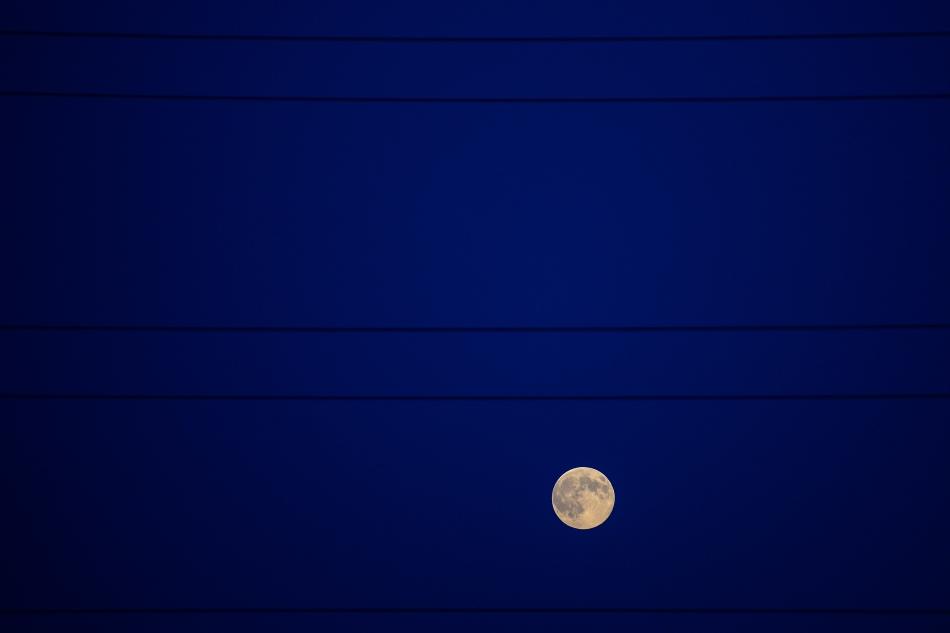 Luna plina poate fi observata printre fire de inalta tensiune, in Bucuresti, duminica, 10 august 2014. Super Luna