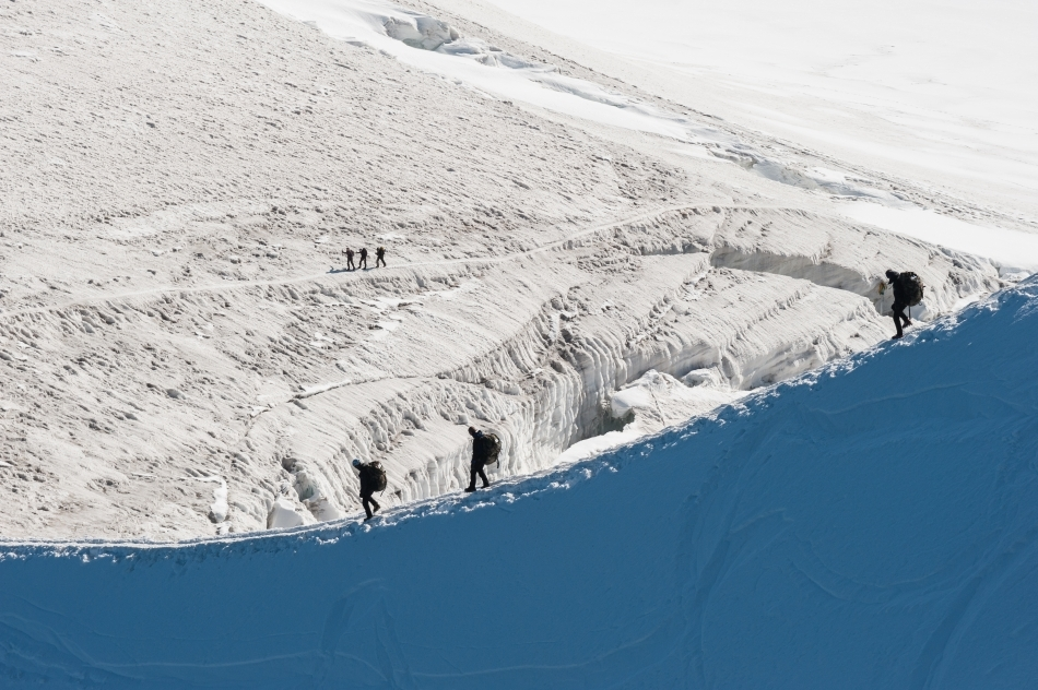 Alpinişti care parcurg iarna o tură de creastă