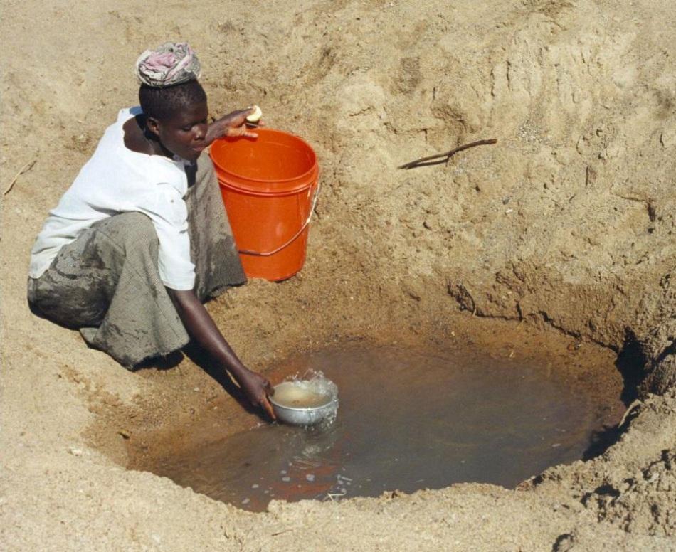 În districtul Meatu din Tanzania, o femeie se strădueşte să colecteze apă pentru nevoile gospodăriei sale.